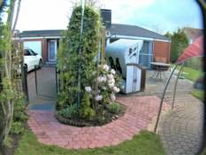 Fotos vom ebenerdigen Ferienhaus Kolks Huus in Neuharlingersiel an der Nordsee zeigen den Zugang zur Terrasse und zum geschlossenen Garten