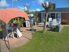 Fotos von Ferienhaus Kolks Huus in Neuharlingersiel zeigen die große möblierte Südterrasse mit bequemer Sitzgarnitur, Strandkorb, Hängesessel und Pavillon